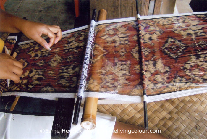 A Geringsing cloth being woven on a back strap loom